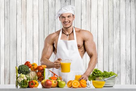 Man bodybuilder cook, cooking freshly squeezed juice and vegetables salad