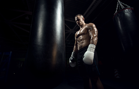 boxer in gym with punching bag, black background, horizontal photo Stock Photo