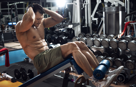 guy bodybuilder , do exercise on abdominal tension in gym, horizontal photo Stock Photo