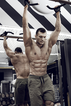 guy bodybuilder , perform exercise do chin-ups, horizontal bar in gym, vertical photo 写真素材