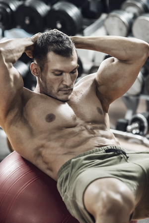 guy bodybuilder , do exercise on abdominal tension in gym, vertical photo