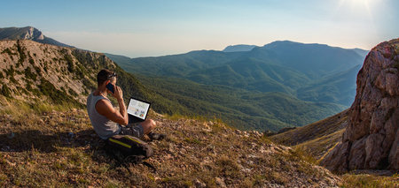 man freelancer sit with laptop, call by cellphone, on beauty mountains landscape, freelance concept
