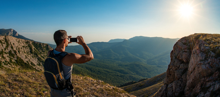 tourist photographing on mobile phone, on beauty mountain landscape background, holiday concept photo, wide panoramic view