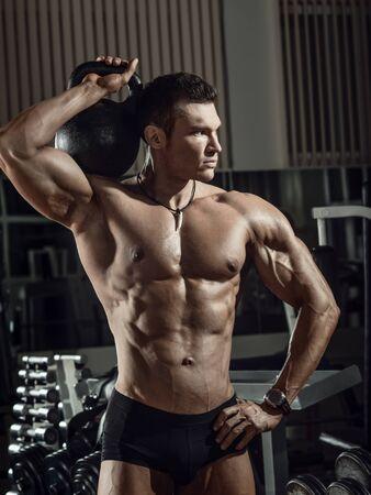 Portrait Kerl Bodybuilder Gewichtheber mit Gewicht, trainiert im dunklen Fitnessstudio