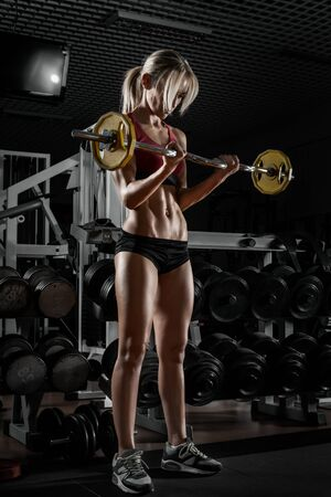 beautiful woman bodybuilder in dark GYM with barbell stand, fitness concept, vertical photo