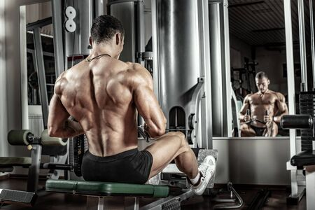 guy bodybuilder, perform exercise with exercise machine horizontal draft on broadest muscle of back, in dark gym