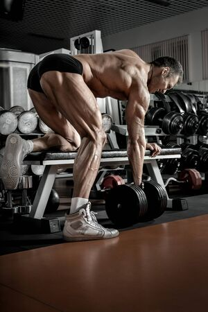 guy bodybuilder perform exercise with dumbbell, trained in dark gym, vertical photo Stock Photo