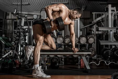 guy bodybuilder perform exercise with dumbbell, trained in dark gym