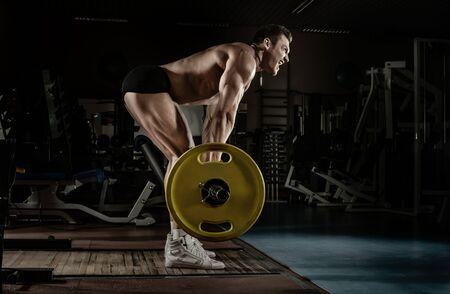 Kerl Bodybuilder führt Übung Kreuzheben mit Langhantel durch, trainiert in dunklem Fitnessstudio