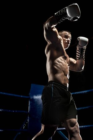 boxer punch jab on boxing ring, on black background