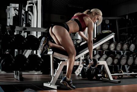 bodybuilder femme faire de l'exercice avec haltère, formé dans une salle de gym sombre