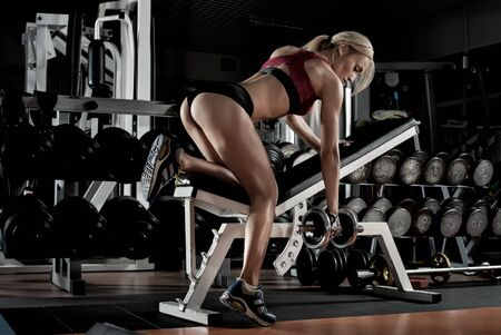 woman bodybuilder perform exercise with dumbbell, trained in dark gym