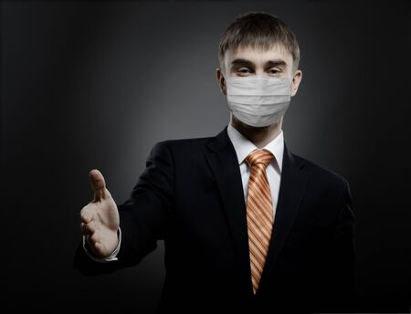 businessman man in medical mask reach out hand for handshake, concept coronavirus covid-19 epidemic