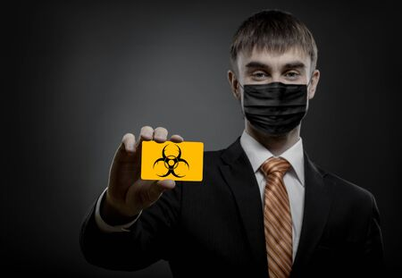 concept coronavirus epidemic, portrait businessman in medical mask show credit card or visiting card 版權商用圖片