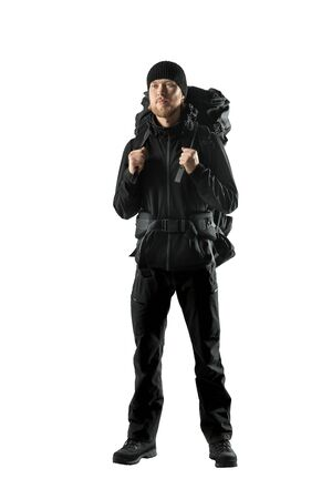 tourist - backpacker in black touristic clothes with backpack and equipment stand on white background, isolated