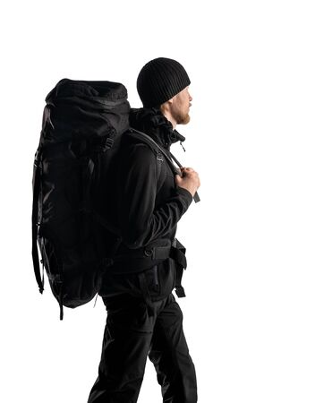 tourist - backpacker in black touristic clothes with backpack and equipment walking on white background, isolated ( sideways )