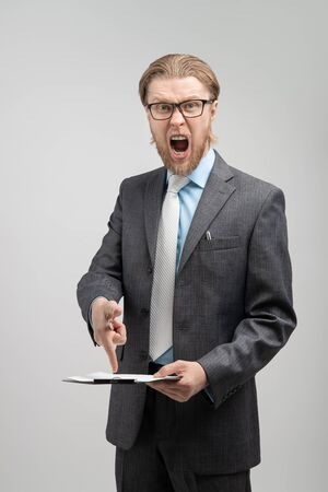 portrait aggressive chief, boss or businessman swearing and screaming ( shout), on gray background