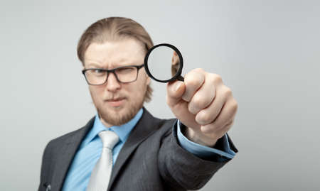 Portrait one man businessman with magnifying glass in hand to consider peering, on gray background, isolated. Stare, gaze concept