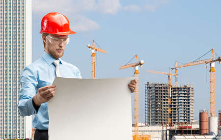 portrait one smart architect worker or engineer man in red construction helmet with drawing - draft, on building site. Building concept