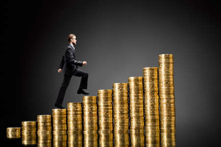 Businessman steps up stairs made of gold coins (money), on dark gray (black) background, isolated