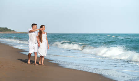 loving couple on seaside in white dress, honeymoon or holiday - vacation concept