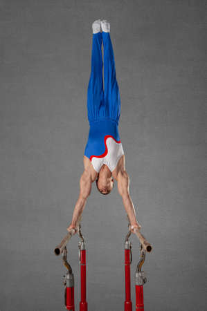 one sportsman gymnast performs a stand on his hands, on gray wall background. Stock Photo