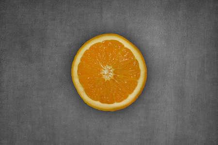 one yellow cut orange, on gray wall background Stock Photo