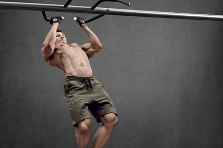 Guy bodybuilder perform exercise do chin-ups, horizontal bar on gray wall background with empty space for text. Gym concept