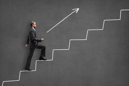 Businessman stepped up by steps, on gray background. Business concept
