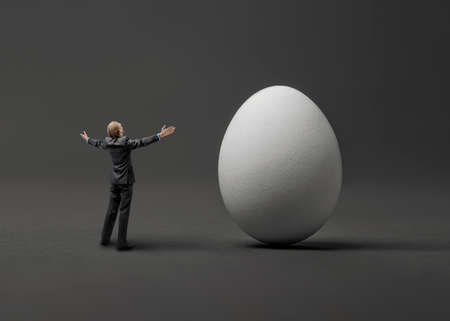 one little businessman with huge white egg, on gray background. Business concept