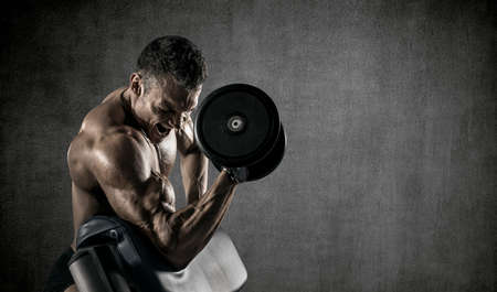 guy bodybuilder, perform exercise with dumbbells, on gray wall background with empty space for text. Gym concept Stock Photo