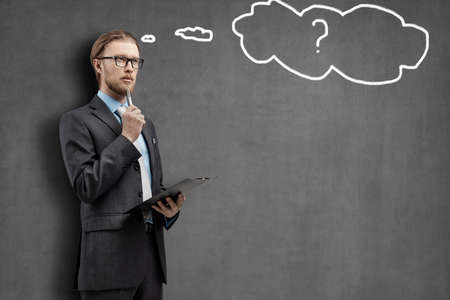 portrait one man businessman or office-worker in glasses spectacles, stand with notebook and thinking, on gray background with empty space for text. Question, issue, problem, idea concept