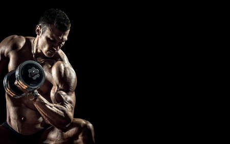 man bodybuilder, perform exercise with dumbbell on black background with empty space. Gym concept