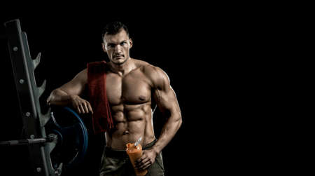 man bodybuilder hold shaker with sportive nutrition - protein of shaker on black background with empty space for text. Gym conncept