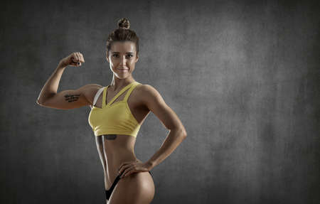 portrait beautiful fitness woman on gray wall background with empty space for text. Gym concept. Stock Photo