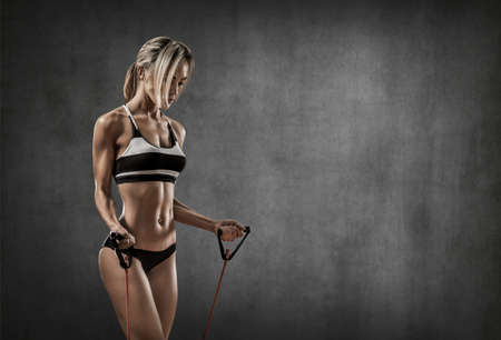 portrait young fitness woman execute exercise on gray wall background with empty space for text, gym concept
