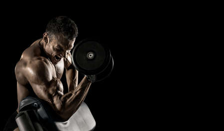guy bodybuilder, perform exercise with dumbbells, on black background with empty space for text. Gym concept