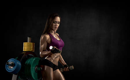 young fitness woman perform exercise with dumbbells on black background with empty space for text. Gym concept