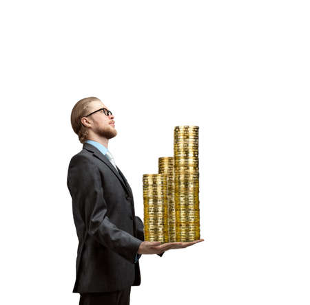 businessman or banker holds in his arms many golden coins, on white background, isolated. Credit or prize winning concept