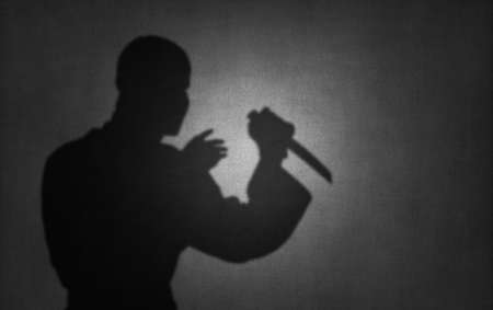 silhouette killer or terrorist with knife, shadow on wall, offence act assassination concept