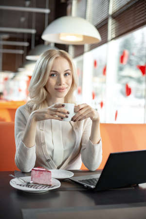 Very beautiful happy young woman, sit in cafe and drink coffee, vertical portrait