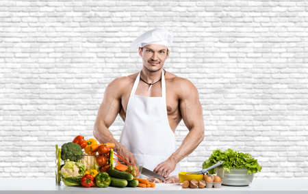 Man bodybuilder in white toque blanche and cook protective apron, concoction vegetables, on white brick wall background. Healthy eating concept