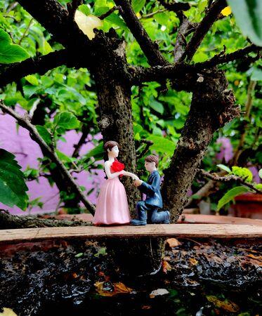 Innovative showpiece image of cute boy and girl on flower pot. Zdjęcie Seryjne