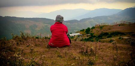 Girl sitting on mountain enjoying the view.