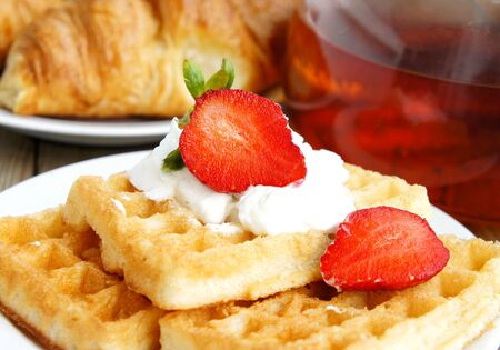 Tasty breakfast - tea, croissants, wafers with cream and strawberries              photo