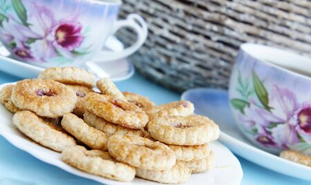 Tea time in the summer garden, tea porcelain cups and biscuits with marmalade  photo