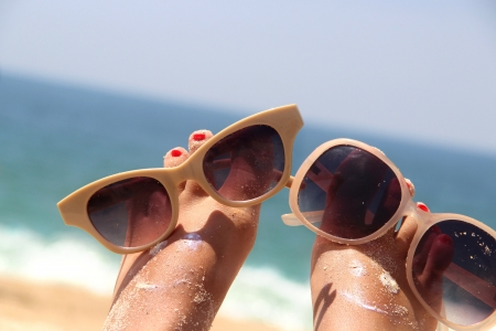 beach feet: Summer holiday - funny female feet in sunglasses Stock Photo