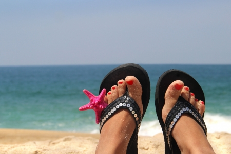 Relaxation on the beach - female feet decorated with sea star