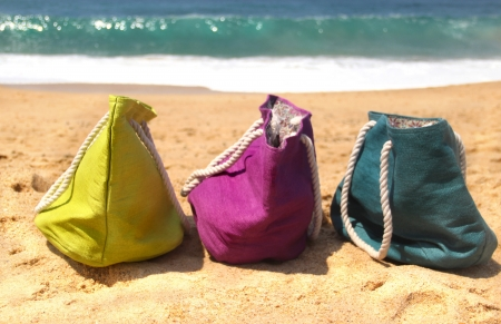 Summer holiday – three vivid bags on the seacoast, green, violet and blue photo