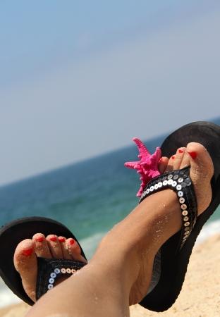 sandalias: Relajaci�n en la playa - pies femeninos adornados con estrella de mar